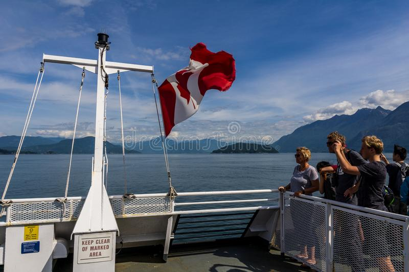 HOWE SOUND, CANADA - JUNE 2, 2019: Canada national flag on BC Ferry with mountains and blue sky. Travel, american, canadian, tourism, tourist, atlantic royalty free stock image