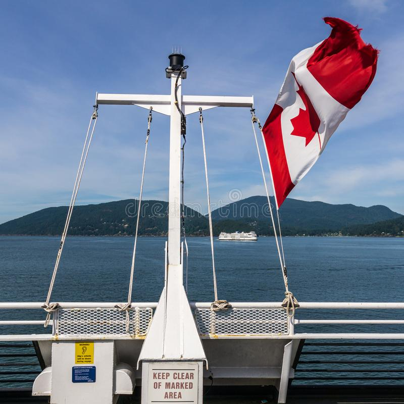 HOWE SOUND, CANADA - JUNE 2, 2019: Canada national flag on BC Ferry with mountains and blue sky. Travel, american, canadian, tourism, tourist, atlantic royalty free stock photography