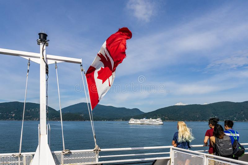 HOWE SOUND, CANADA - JUNE 2, 2019: Canada national flag on BC Ferry with mountains and blue sky. Travel, american, canadian, tourism, tourist, atlantic stock photos