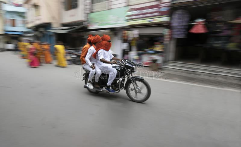 3 person riding bike on a local street of rajasthan royalty free stock image
