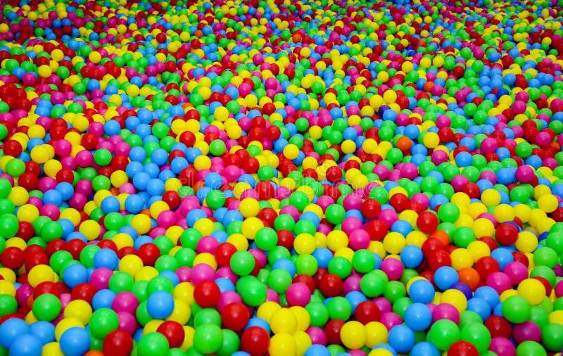 Hoyo de la bola con las bolas pl?sticas coloridas en centro de entretenimiento de los ni?os Re?na con el fondo brillante de las b foto de archivo libre de regalías