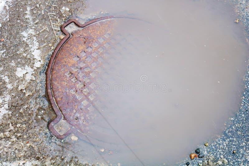 Hoyo del asfalto llenado de agua imagenes de archivo