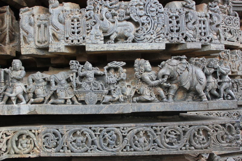 Hoysaleswara Temple wall carving depicting a demon fighting with an elephant royalty free stock photography