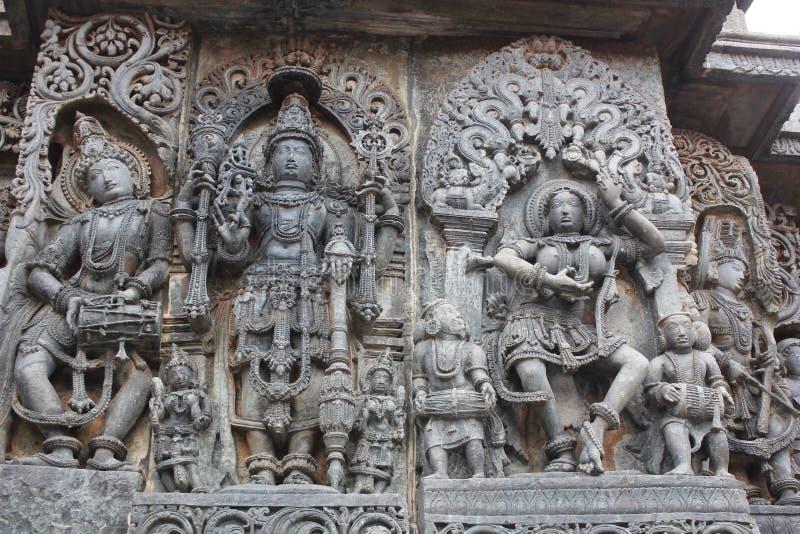 Hoysaleswara Temple Wall carving showing lord Mahavishnu inbetween a female dancer and a male musician royalty free stock image