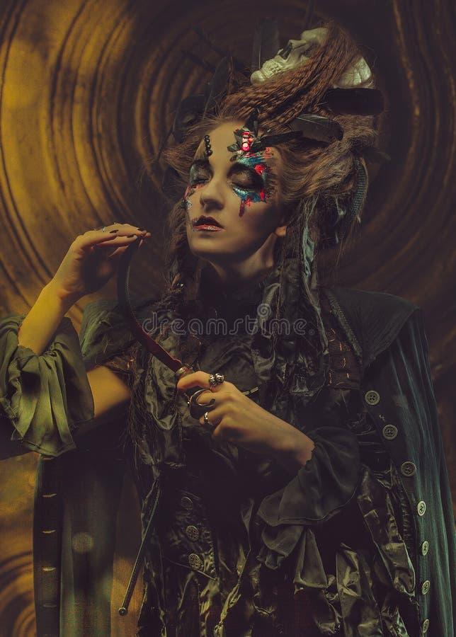 Hoz hloding de la bruja joven Brillante componga, cráneo, tema de Halloween del humo fotografía de archivo libre de regalías