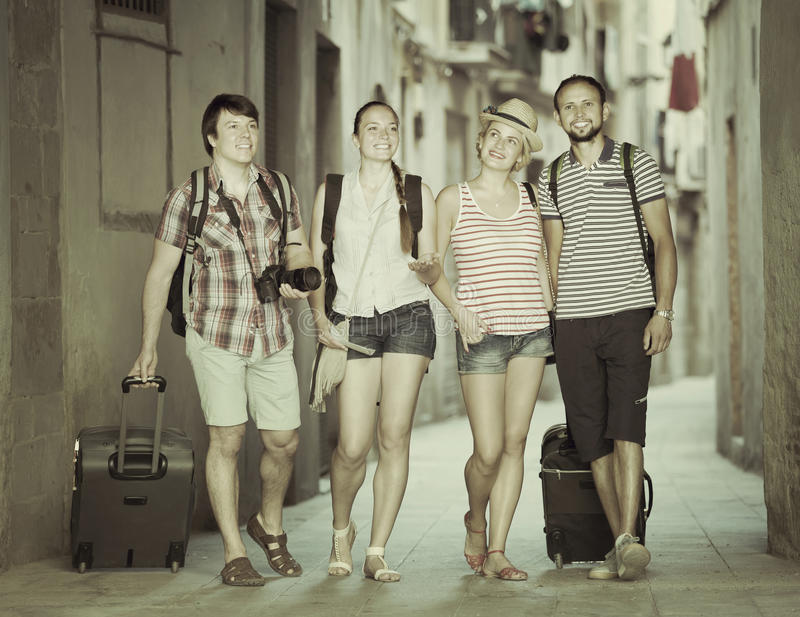 Hppy tourists at the street with luggage royalty free stock image