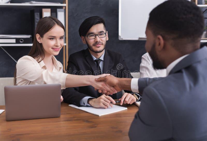 HR经理与申请人握手在采访 免版税库存照片