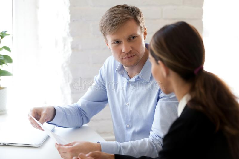 Hr manager and applicant sitting at desk during job interview. Boss holding cv listening female applicant. Serious business partners discussing financial report stock photo