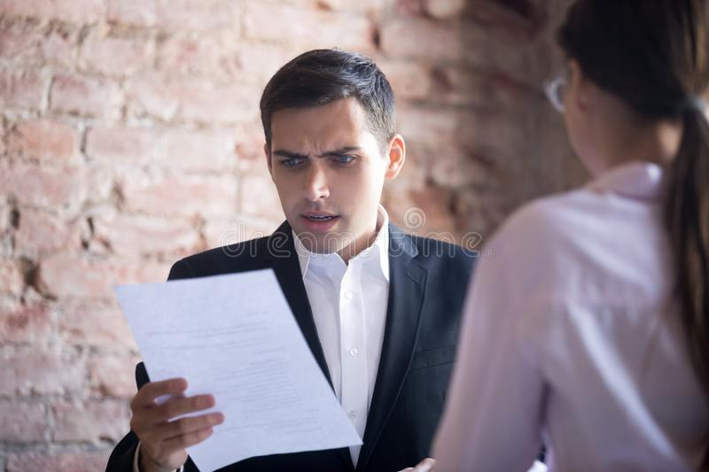 HR manager is dissatisfied with resume of female applicant. Funny HR manager is dissatisfied with resume of female applicant. Skeptic men is unpleasantly royalty free stock image