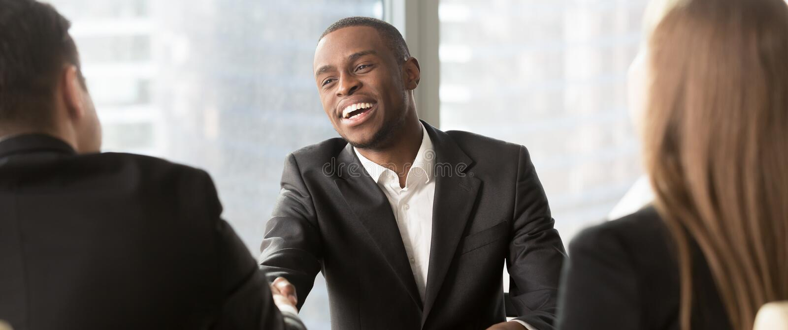 Hr manager handshaking congratulating black candidature with successful job interview royalty free stock photo