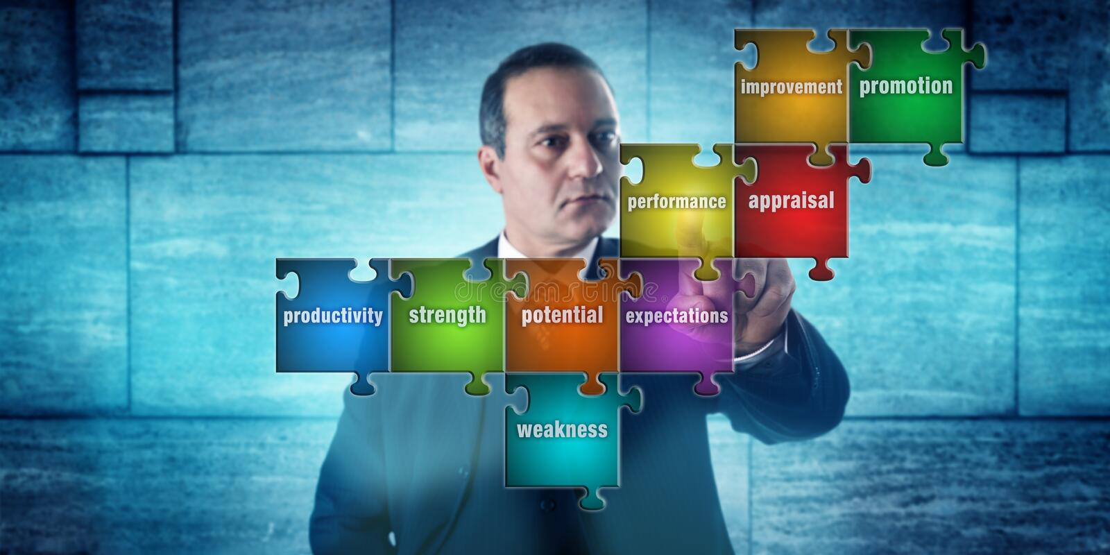 HR Manager Selecting Performance Appraisal Terms. HR manager with focused look touching a jigsaw puzzle imprinted with performance appraisal terms. Concept for royalty free stock images