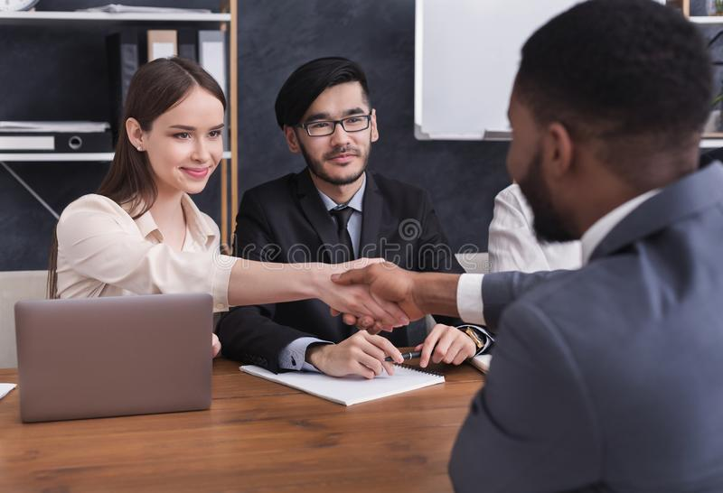 HR manager shaking hands with applicant at interview. HR manager shaking hands with african-american applicant after interview royalty free stock photos