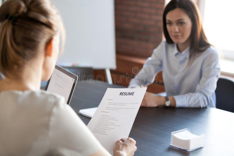 HR mangers hiring millennial female job candidate. Back close up view of female employer holding applicant resume during office interview, millennial work stock photos