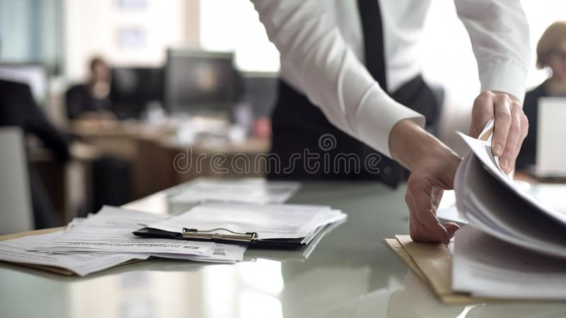 HR officer searching resume in stack of papers, preparing documents for meeting. Stock photo royalty free stock photo