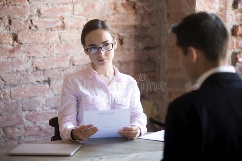 HR young manager woman interviewing male in the office. Serious HR young manager women interviewing male in the office. Suspicious female holding curriculum stock images