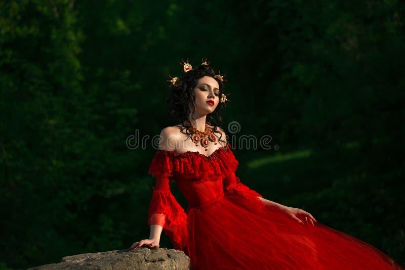 Hrabina w długim czerwieni sukni obsiadaniu z jego przygląda się zamkniętego fotografia royalty free