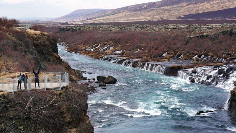 hraunfossar瀑布的愉快的亚裔家庭旅客在冰岛 免版税库存照片