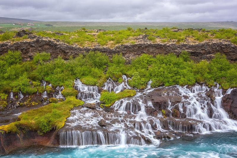Hraunfossar waterfalls or Lava Falls, Iceland. Beautiful summer landscape. Water is flowing through the lava rocks into the emerald colored Hvita river. One of stock photo