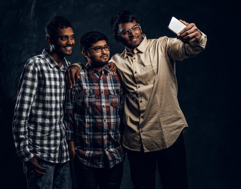 Hree черно-сняло кожу с друга в рубашках усмехаясь и представляя стоковая фотография