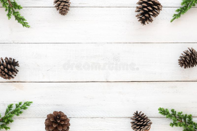 Hristmas frame made of fir leaves and pine cones decoration rustic elements on white wooden stock photography