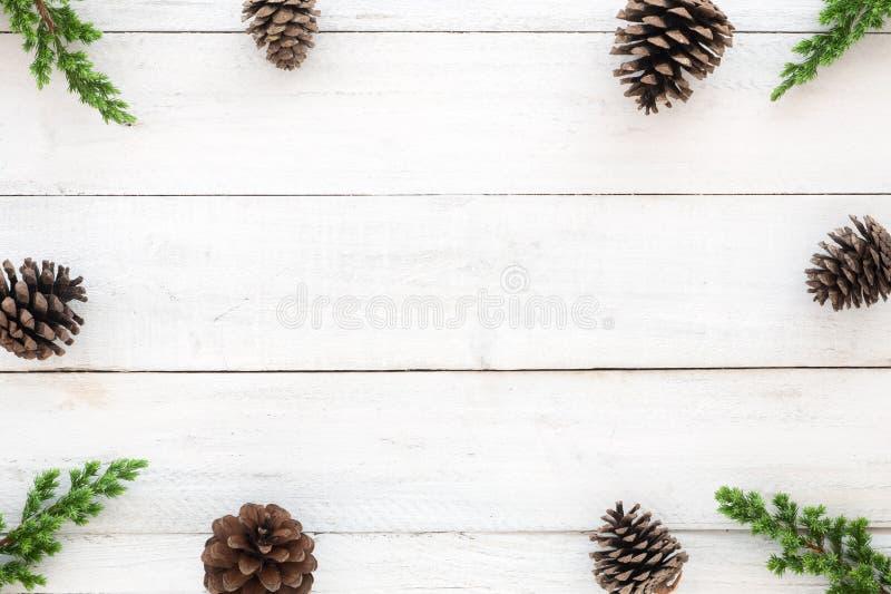 Hristmaskader van van sparbladeren en denneappels decoratie rustieke elementen dat wordt gemaakt op witte houten stock fotografie