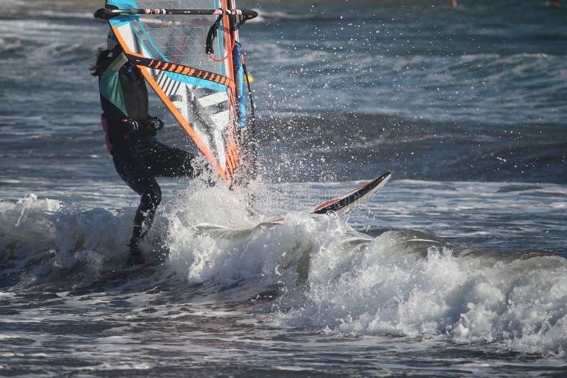 Hrough fale Dziewczyna windsurfing przy Atlantyckim oceanem/El Medano, Tenerife, Hiszpania zdjęcia royalty free