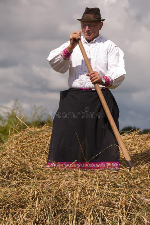 HRUSOV, ESLOVÁQUIA - 16 DE AGOSTO: Fazendeiro idoso no traje tradicional que relaxa durante o festival Hontianska Parada do folcl fotografia de stock royalty free