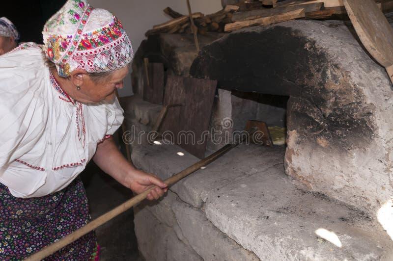 HRUSOV, ESLOVÁQUIA - 16 DE AGOSTO: Mulheres superiores no traje tradicional que prepara o pão fresco durante o festival Hontiansk imagem de stock royalty free