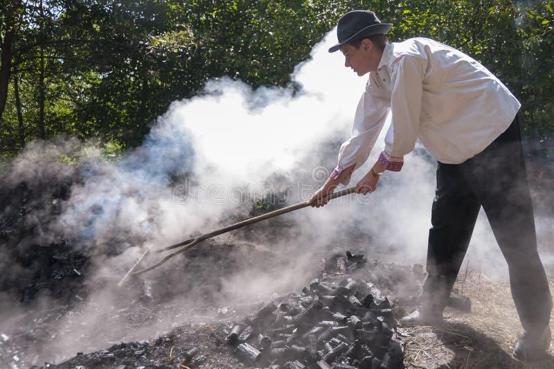 HRUSOV, ESLOVÁQUIA - 16 DE AGOSTO: O trabalhador novo no traje tradicional faz o carvão vegetal durante o festival Hontianska Par fotografia de stock royalty free