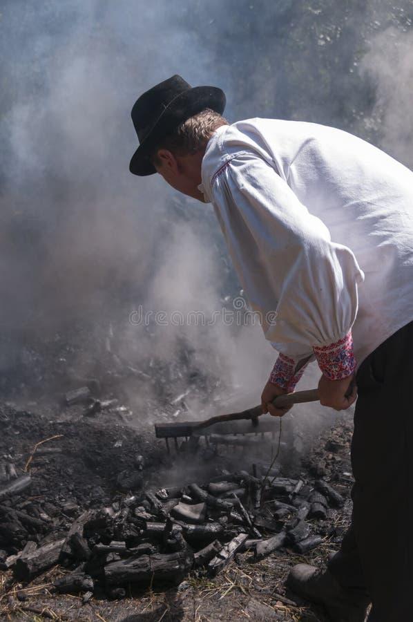HRUSOV, ESLOVÁQUIA - 16 DE AGOSTO: Wworker no traje tradicional faz o carvão vegetal durante o festival Hontianska Parada do folc foto de stock