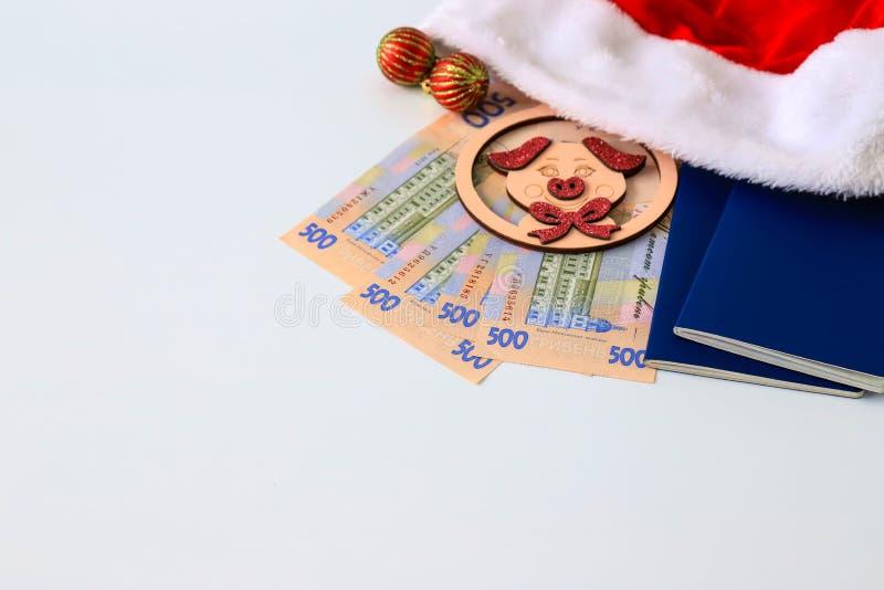 Hryvna ucraniano, hryvnia de los billetes de banco 500, con el cerdo del juguete 2019, sombrero rojo de Santa Claus y pasaporte a foto de archivo