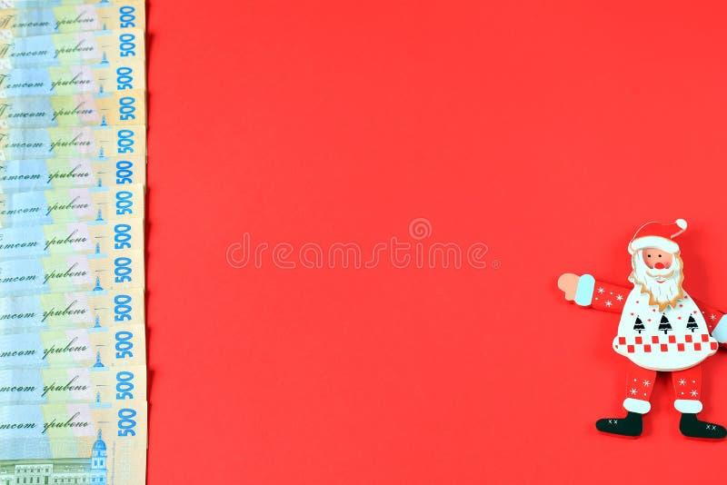 Hryvna ucraniano, hryvnia de los billetes de banco 500, con el juguete Santa Claus en fondo rojo, concepto del dinero, la Navidad fotografía de archivo libre de regalías