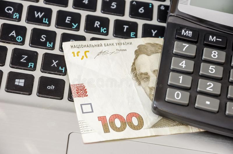100 hryvnia banknotes and calculator on a laptop keyboard, closeup. Ukrainian money on the keyboard. 100 hryvnia banknotes and calculator on a laptop keyboard royalty free stock images