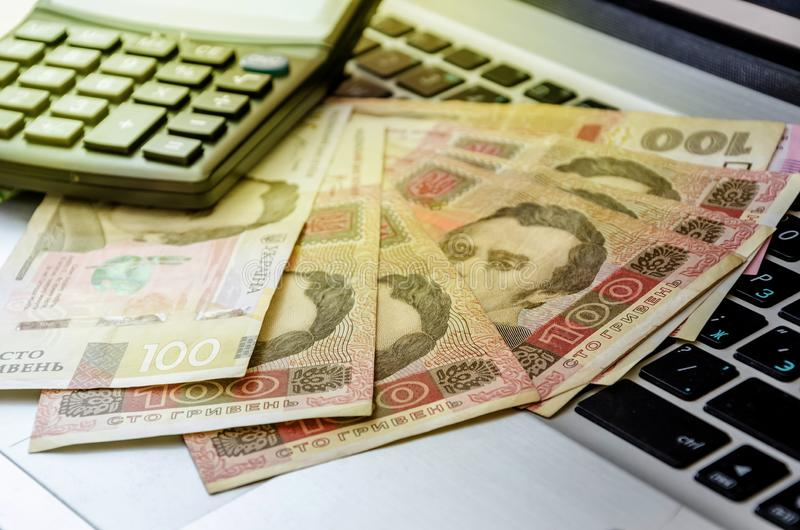 100 hryvnia banknotes and calculator on a laptop keyboard, closeup. Ukrainian money on the keyboard. 100 hryvnia banknotes and calculator on a laptop keyboard stock images