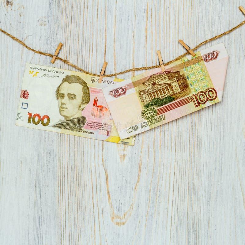 Hryvnia ucraniano e rublos de russo suspendidos em pregadores de roupa Lavagem de dinheiro, fraude da moeda e conceito da corrupç fotografia de stock royalty free