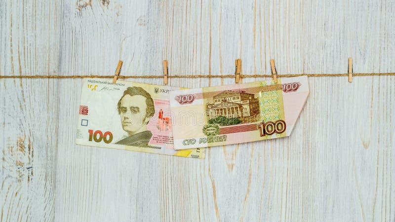 Hryvnia ucraniano e rublos de russo suspendidos em pregadores de roupa Lavagem de dinheiro, fraude da moeda e conceito da corrupç foto de stock