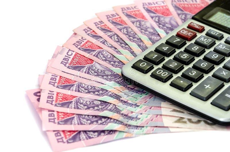 Hryvnia zweihundert und ein Taschenrechner auf einem weißen Hintergrund stockfoto