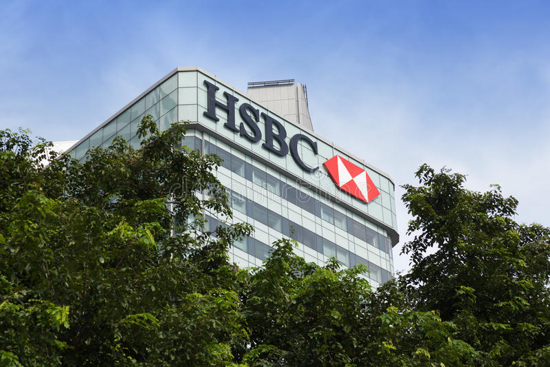 HSBC building in Singapore. Hongkong and Shanghai Banking Corporation (HSBC) office building, rising above canopy of trees and against blue sky, in the Central stock photography