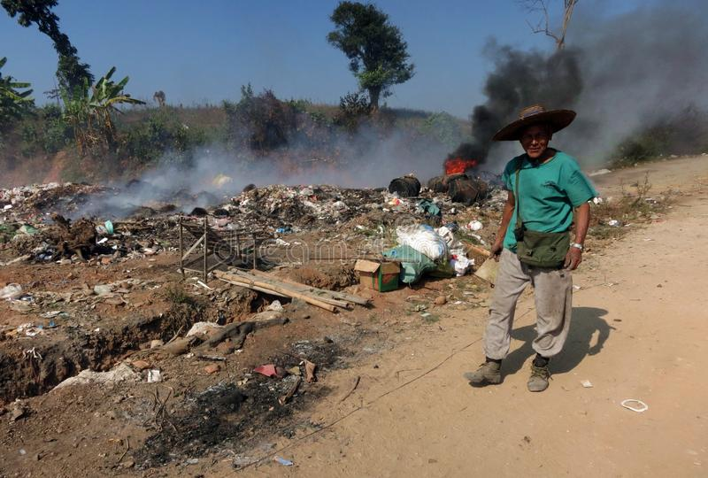 A smiling Burmese man standing in front of a pile of burning trash stock photos