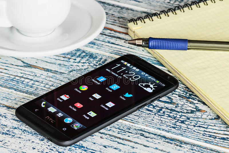 HTC-mobiltelefon med Android applikationer på skrivbordet royaltyfri foto