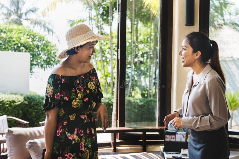 Huésped de las mujeres que habla con el recepcionista en un pasillo del hotel imagen de archivo libre de regalías