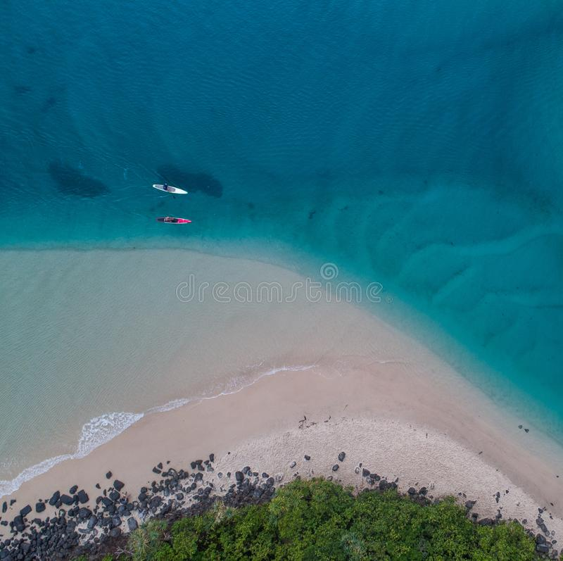 Huésped y canoa de la paleta en el agua azul en la salida del sol imagen de archivo libre de regalías