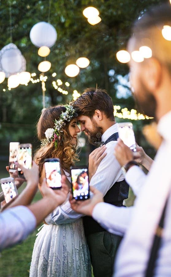 Huéspedes con los smartphones que toman la foto de la novia y del novio en la recepción nupcial afuera foto de archivo