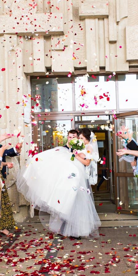 Huéspedes que lanzan confeti sobre la novia y el novio At Wedding imagen de archivo