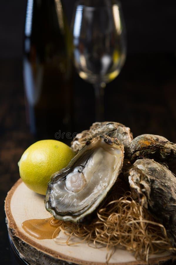 Huîtres et vin blanc sur les fruits de mer en bois de fond photographie stock