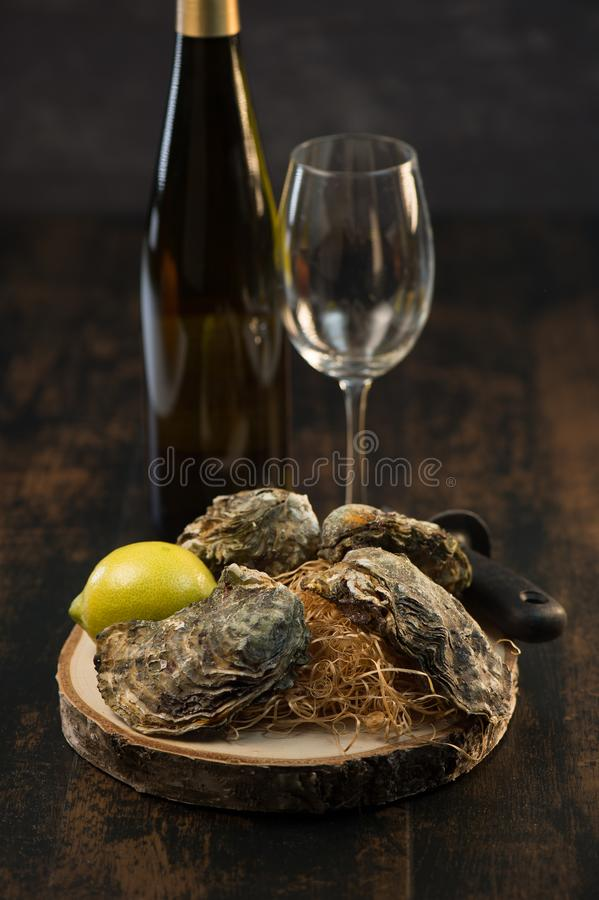 Huîtres et vin blanc sur les fruits de mer en bois de fond image stock