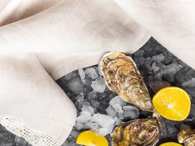 huîtres fraîches crues sur glace avec tranches de citron, mollusque de l'océan Atlantique sur serviette en lin images stock