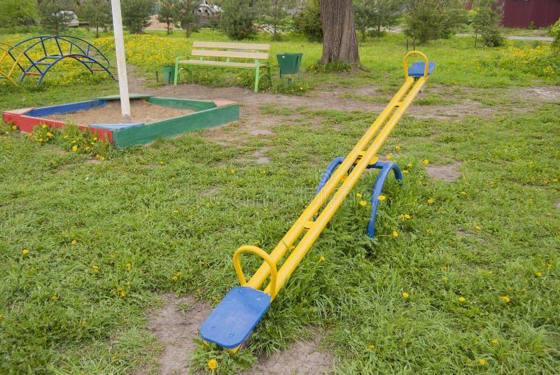 Huśta się dla dzieci, kolor żółty z błękitnymi siedzeniami fotografia stock