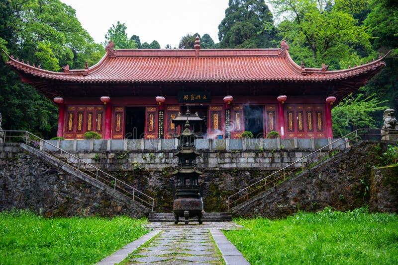Huanglong gulnar den buddistiska templet för draken i mitt av skogen i den Lushan nationalparken i Kina royaltyfri fotografi