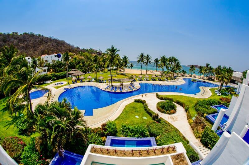 Huatulco, Messico - 14 aprile 2012 Vista del balcone sulla piscina e della spiaggia dell'oceano Pacifico fotografia stock libera da diritti